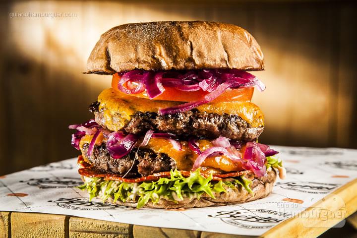 pão australiano, maionese defumada picante, alface frise, crispy de peperone, 2 burgers da casa 100g, cheddar derretido, cebola roxa em conserva, tomate acompanha chips de batata - R$ 32 - Bertolas Burger & Food