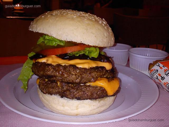 2 hambúrgueres bovinos, queijo cheddar, maionese de wasabi, chutney de cebola roxa, pimenta jalapeño, picles, molho barbecue, alface americana e tomate caqui