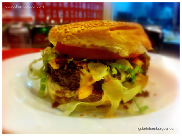 Hambúrguer bovino, queijo cheddar, bacon, alface, tomate e maionese tradicional