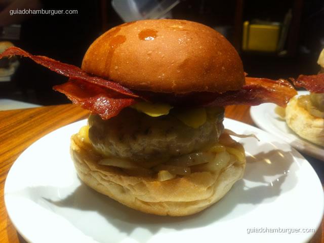 O Hambúrguer do Bacon Bovino, preparado com um hambúrguer de 180g, queijo prato, cebola defumada, picles da casa e bacon bovino