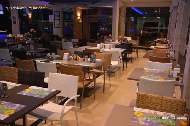 Ambiente com mesas de 6 pessoas e 2 pessoas nas janelas - Hamburgueria da Mooca