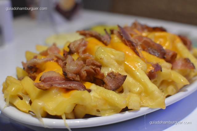 Detalhe da batata coberta de queijo, cheddar e bacon crocante - Hamburgueria da Mooca