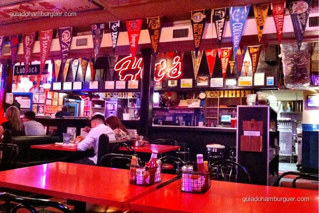 Ambiente super decorado com bandeiras de times, mesas de fórmica e luminoso em neon - Hut's Hamburgers