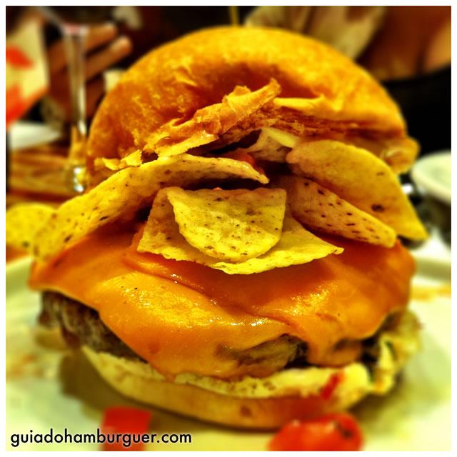 El Nacho: hambúrguer de 150g, servido com queijo cheddar, maionese, pico de gallo, nachos e relish de milho no pão sem gergelim - America