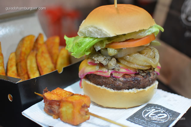Hambúrguer 498: Pão de hambúrguer tradicional, hambúrguer artesanal bovino, shimeji grelhado, queijo gouda, salada (picles e cebola tostada) e acompanhado de espeto de queijo coalho envolto em pancetta e melaço de cana. - Hamburgueria 162 Express