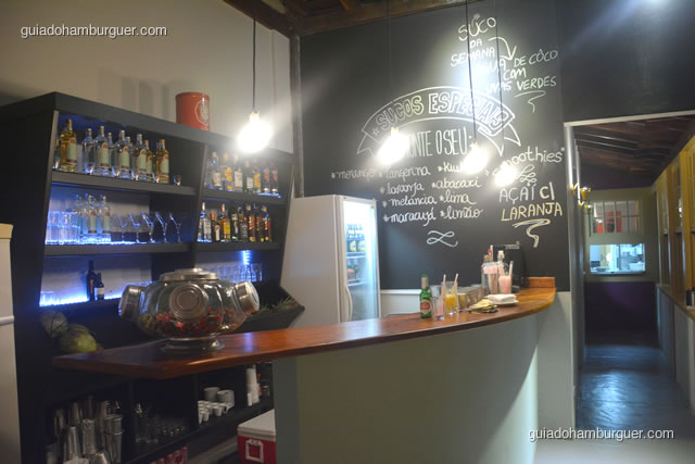 Bar com lousa grande e bebidas na parede - Dona Maricota