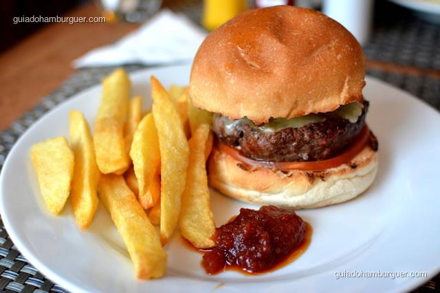 Hambúrguer com queijo, tomate, cebola caramelada e picles. As batatas rústicas e o chutney de tomate acompanham - 12 Burguer e Bistrô