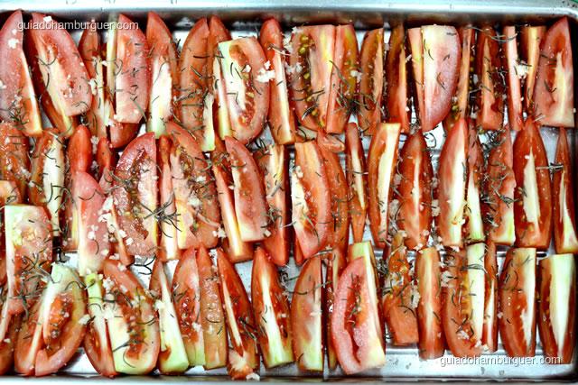 Coloque os tomates na bandeja e tempere