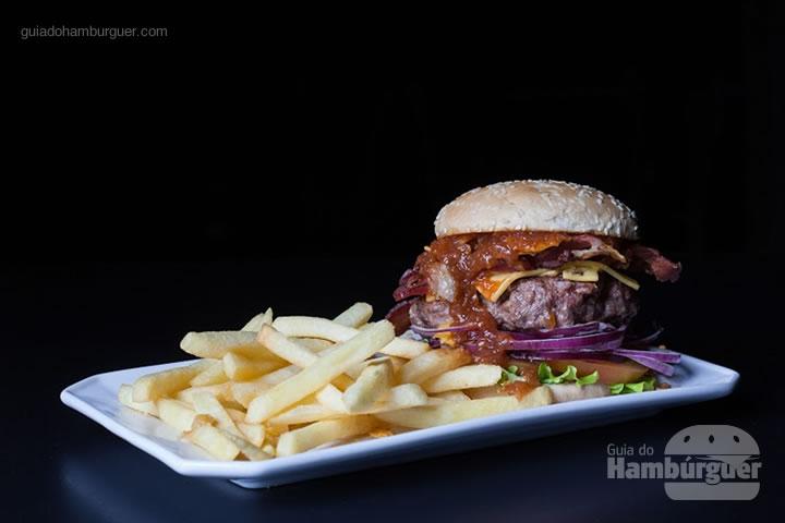 Metrópole, pão, blend da casa, porção dupla de queijo prato, bacon, farinha de nachos, alface, tomate e cebola roxa) por R$ 32,00 - 8º UOL Burger Fest Belo Horizonte