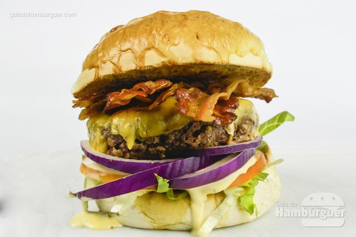 Taubatexas, pão de cebola, hambúrguer artesanal de 150g, queijo prato, cebola roxa, alface americana, tomate, bacon e horsey sauce