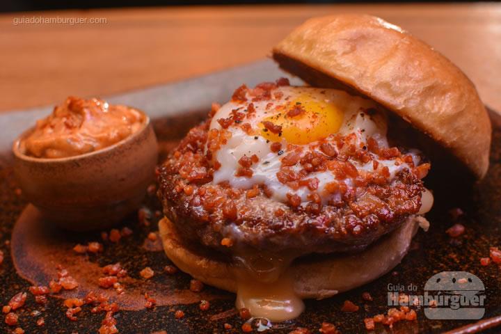 hambúrguer com blend de Wagyu e Angus moldado com uma crosta de bacon, recheado com queijo Maasdam Holandês e um ovo  perfeito por cima e servido no pão brioche. Servido com uma maionese especial defumada