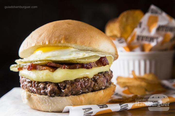 hambúrguer com ovo, picles, pedaços de bacon e queijo raclete derretido no pão de hambúrguer. Acompanha chips de batata – R$ 28 - Ambar Cervejas Artesanais