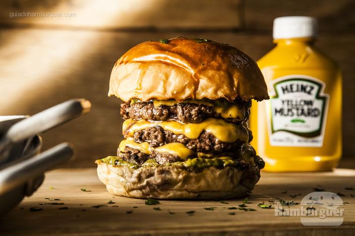 Burger gigante em sabor com tres carnes fininhas de 80g, queijo cobocó derretido, cebola roxa e maionese verde da casa no pão de brioche - R$ 28 - Blue Sandwich Market