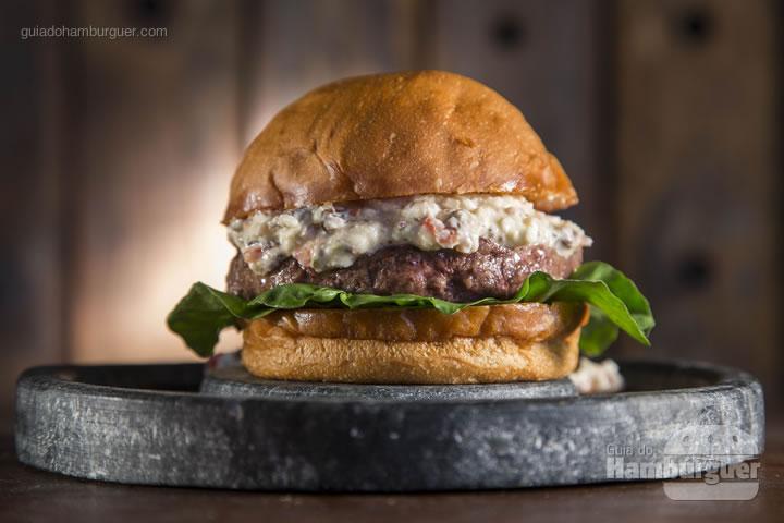 Hambúrguer de 180G do blend secreto da casa, pasta de queijo Feta com pimentão vermelho, tomate italiano, cebola roxa, azeitonas pretas e azeite de oliva, folhas de rúcula, servido no pão branco artesanal, feito na própria casa -  R$ 29,90 Combo Burger + Budweiser R$ 37,11 - Hamburgueria Tradi