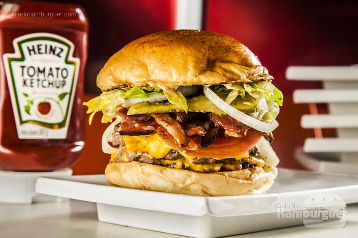 Dois hambúrgueres de 120g servidos no pão brioche, cobertos por american cheese e acompanhados por alface americana, cebola, tomate, picles de pepino e molho especial levemente picante - R$ 30 - Pibus Hamburger