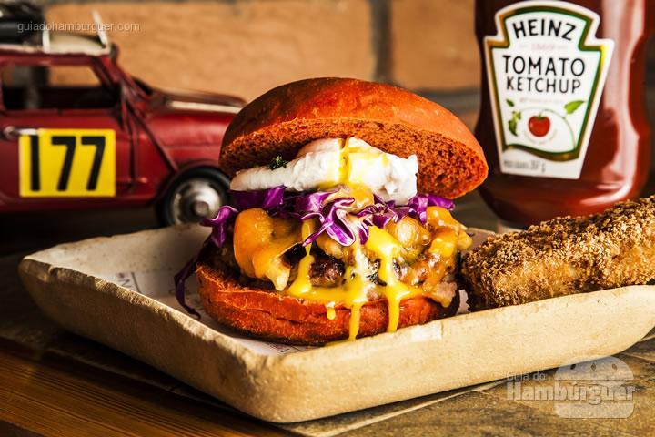 Pão vermelho, hambúrguer de costela suína bbq, panceta, queijo cheddar inglês, cebola caramelizada, ovo, salsa, repolho roxo e  purê de maçã ao vinho. Acompanha uma costelinha suina bbq. - Vinno Tinto Burger