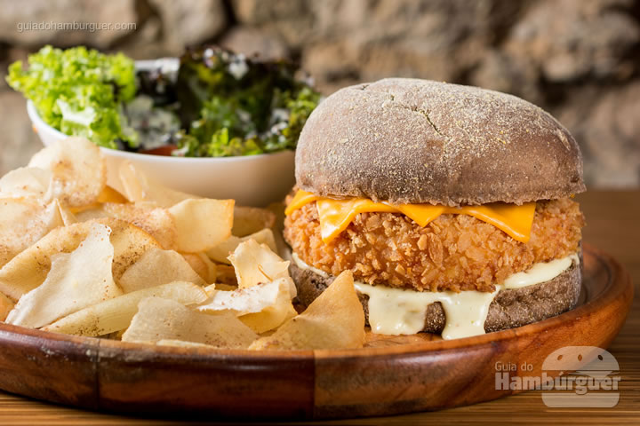 Hambúrguer com 180g de frango com bacon empanado na farinha panko, com queijo cheddar, servido no pão australiano com molho aioli de limão siciliano acompanhado de batata frita ou chips de aipim e salada da casa. R$ 31,90  - Casarão 1903