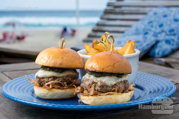 2 Mini Burgers de cordeiro, temperados com sal, pimenta preta e alho, pão artesanal e molho pesto de hortelã com batatas assadas com alho, ervas e parmesão. R$29,90 - Clássico Beach Club