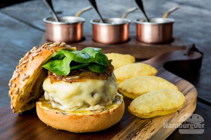 Hambúrguer de Baby Beef Brangus com azeite trufado, lâminas de queijo manchego, cebola caramelizada, rúcula, molho béarnaise em um pão artesanal com sementes de girassol. R$ 55,00  - Rubaiyat Rio