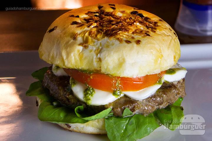 Cosa Nostra - pão de cebola, blend bovino angus 180g, muçarela de búfala, tomate caqui, rúcula e pesto de manjericão por R$ 33,90