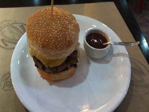 Hambúrguer de costelinha de porco, com aproximadamente 2cm de altura, juntamente com queijo prato derretido e cebola caramelada e acompanhado de molho barbecue por R$ 19,50 - Hamburgueria 162