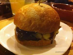 Santo Hambúrguer com hambúrguer de picanha, queijo ementhal, confit de cebola, maionese e molho barbecue no pão caseiro rústico